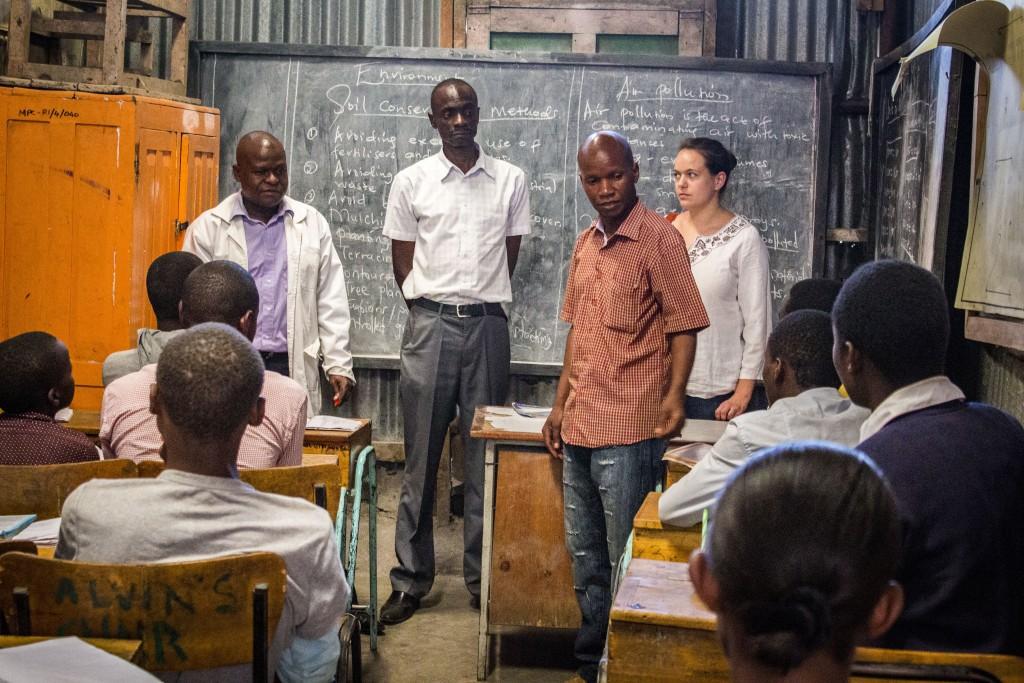 Charles Ogutu (v červenej košeli) v jednej z tried, kde prebieha kurz pre dospelých, ktorí so dokončujú základné vzdelanie. Na fotke sa prihovára študentom počas návštevy Koordinátorky Dobrej noviny.